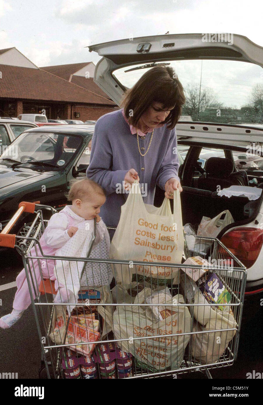 mother placing groceries into the boot of her car with toddler in trolley seat - Stock Image