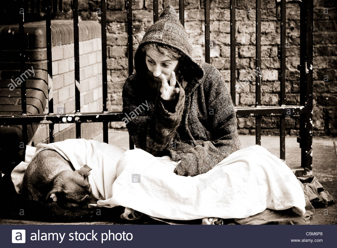 Homeless man with his dog sitting on the floor who became angry and aggressive during the portrait session - London Stock Photo