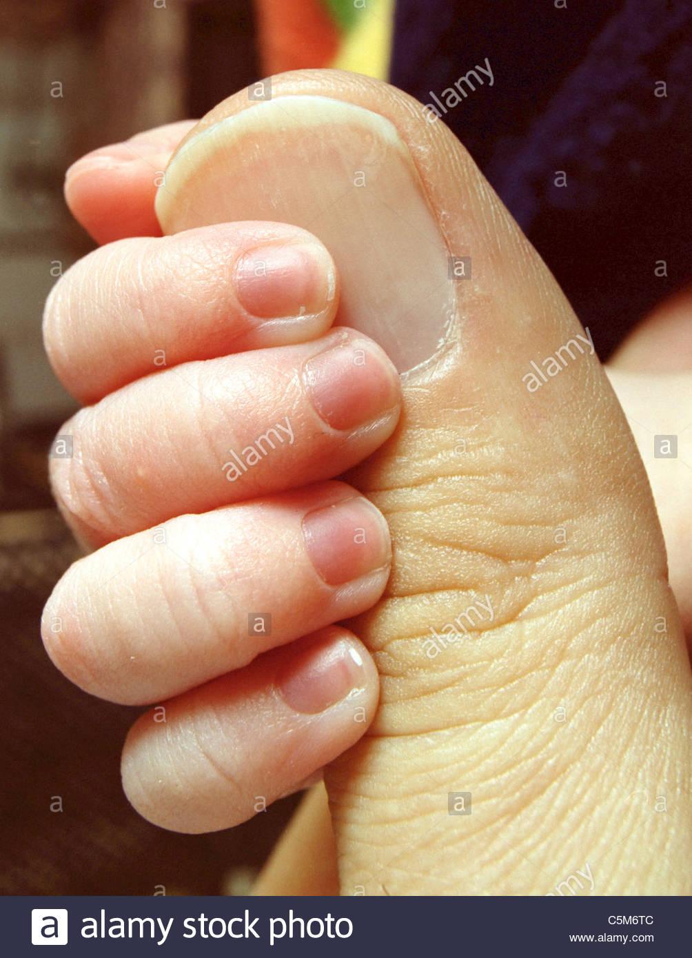 Newborn baby hand holding fathers thumb fingernails boy Stock Photo