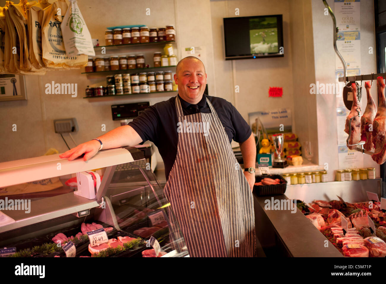 A happy smiling jolly fat Butcher in his shop, Aberystwyth wales UK - Stock Image