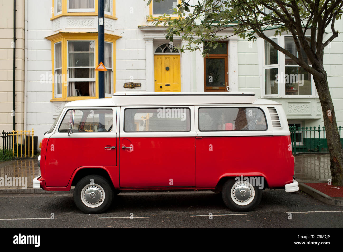 a red and white VW Campervan parked on the street, UK - Stock Image