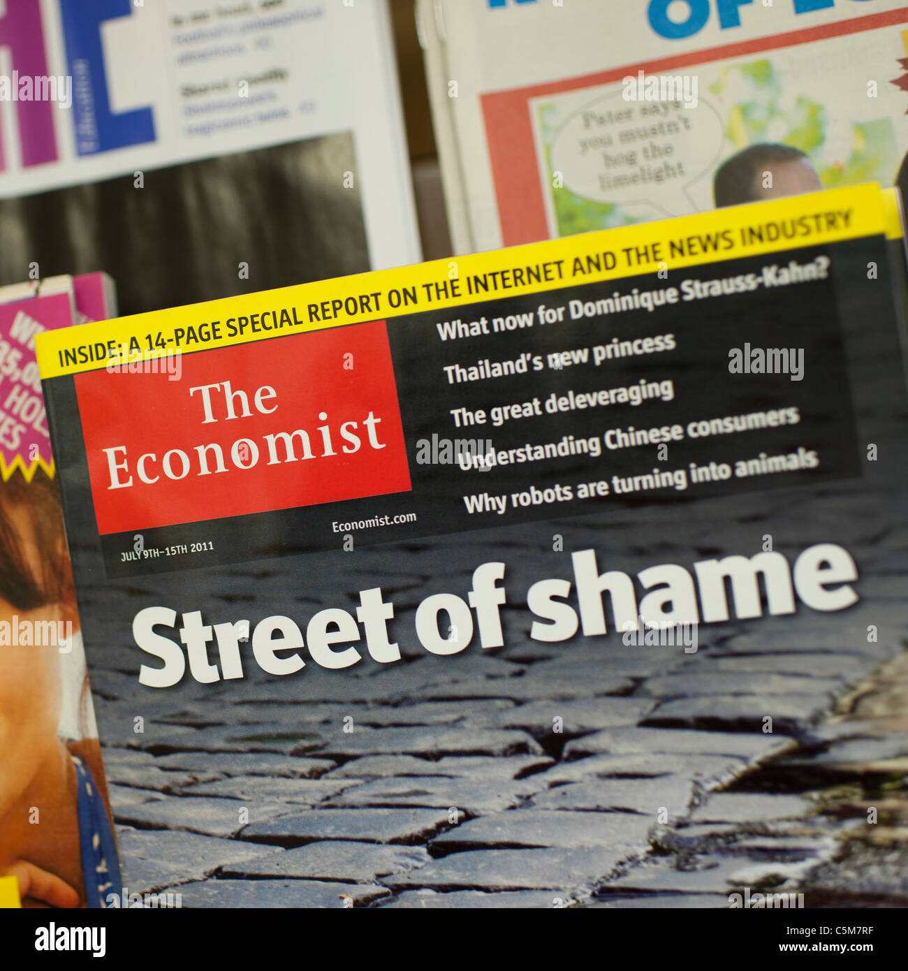 Front covers of the economist weekly magazines in a newsagents shop UK - Stock Image
