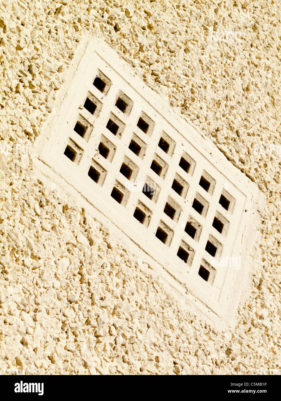 Air brick used for ventilation on the outside of a house with white painted rendering - Stock Image