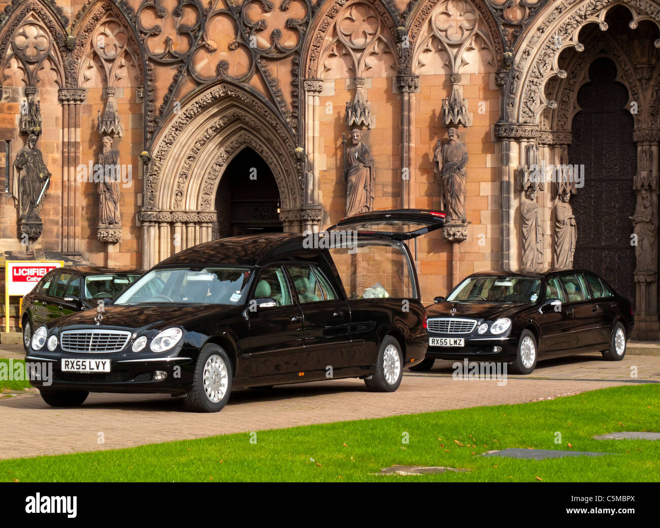 Funeral hearse and stretched Mercedes limousines parked outside Lichfield Cathedral in Staffordshire England UK - Stock Image