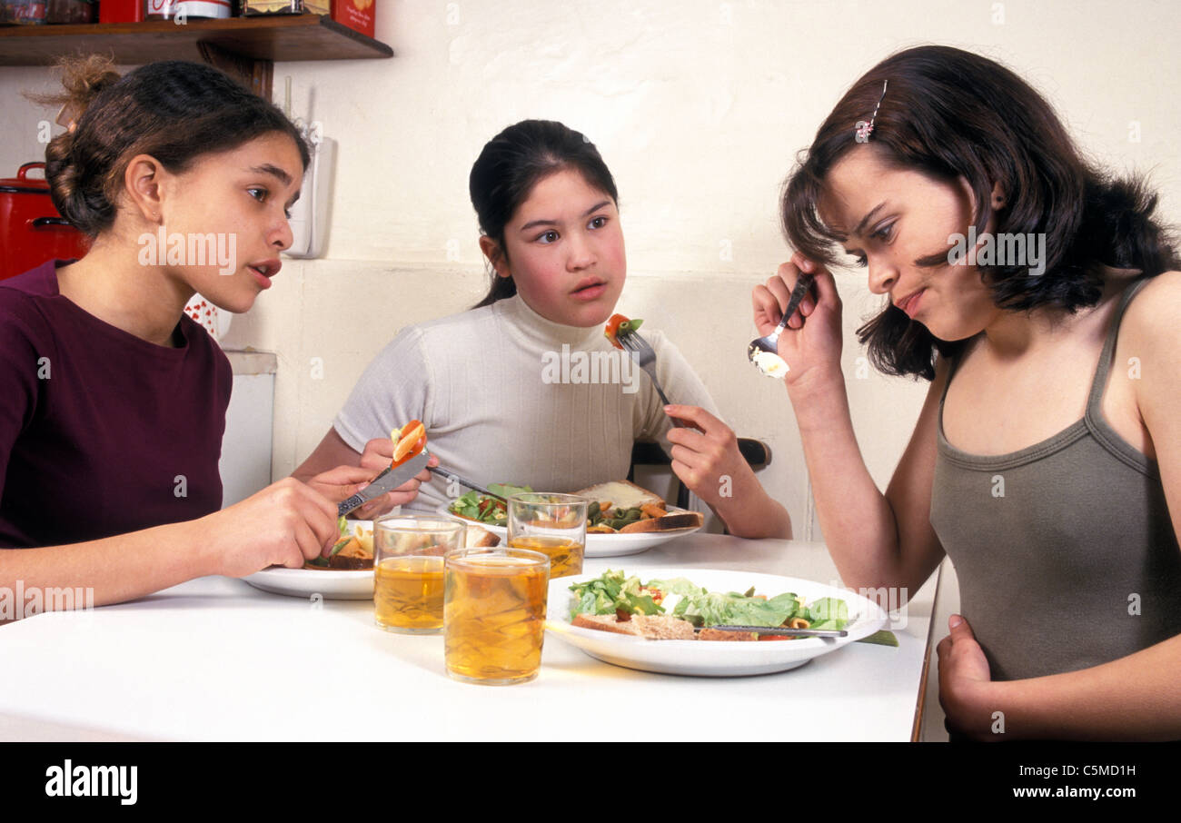 girl with eating disorder having meal with friends - Stock Image