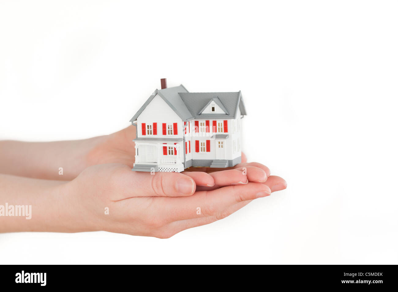 Hands holding a miniature house on a white background - Stock Image