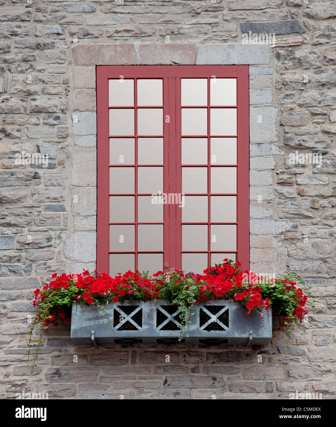 Front view of an old window and a flowerbox on an old stone building. - Stock Image