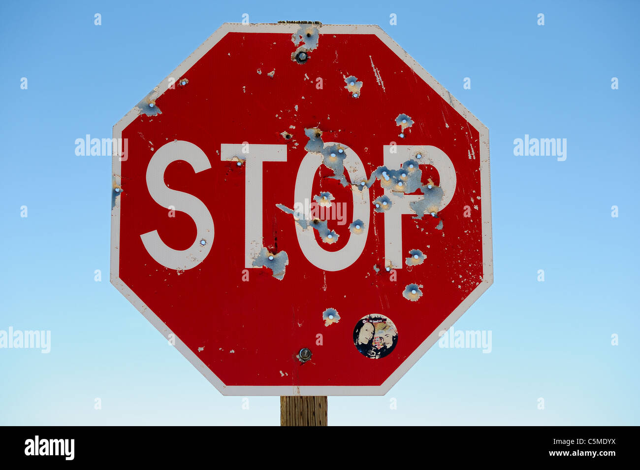 Bullet Holes in a Stop sign on a road in desert near Monument Valley Navajo Tribal Park in Utah, USA - Stock Image