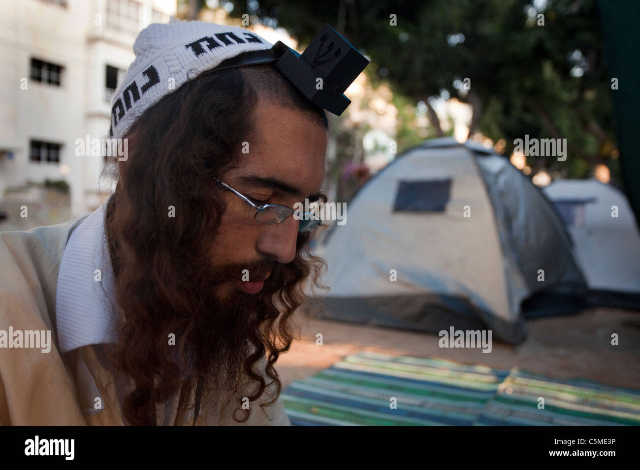 A follower of the Breslov Hassidic Jewish movement praying in the Tent City compound in Rothschild avenue in Central - Stock Image