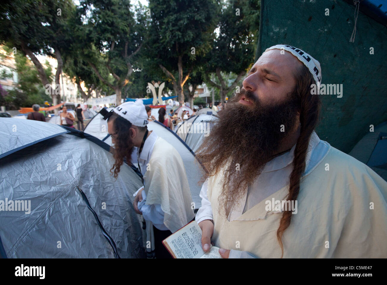 Followers of the Breslov Hassidic Jewish movement praying in the Tent City compound in Rothschild avenue in Central - Stock Image