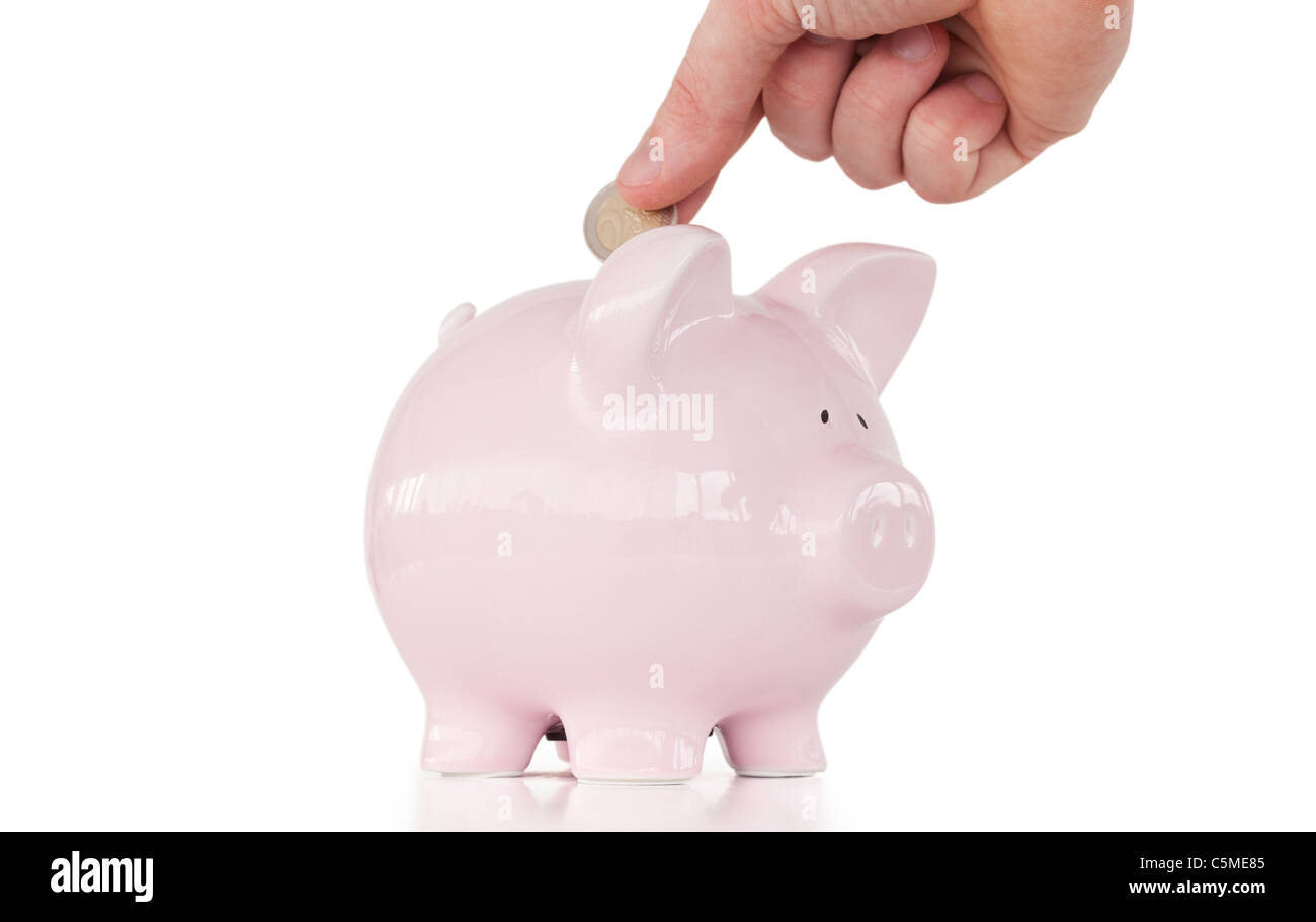 Hand inserting a coin in a pink piggy bank Stock Photo