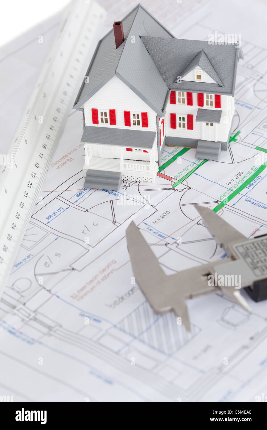 Top view of toy house model and caliper on a plan - Stock Image