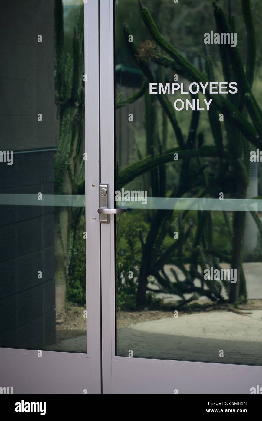 Modern Glass Door With Reflection And Employees Only Sign Stock