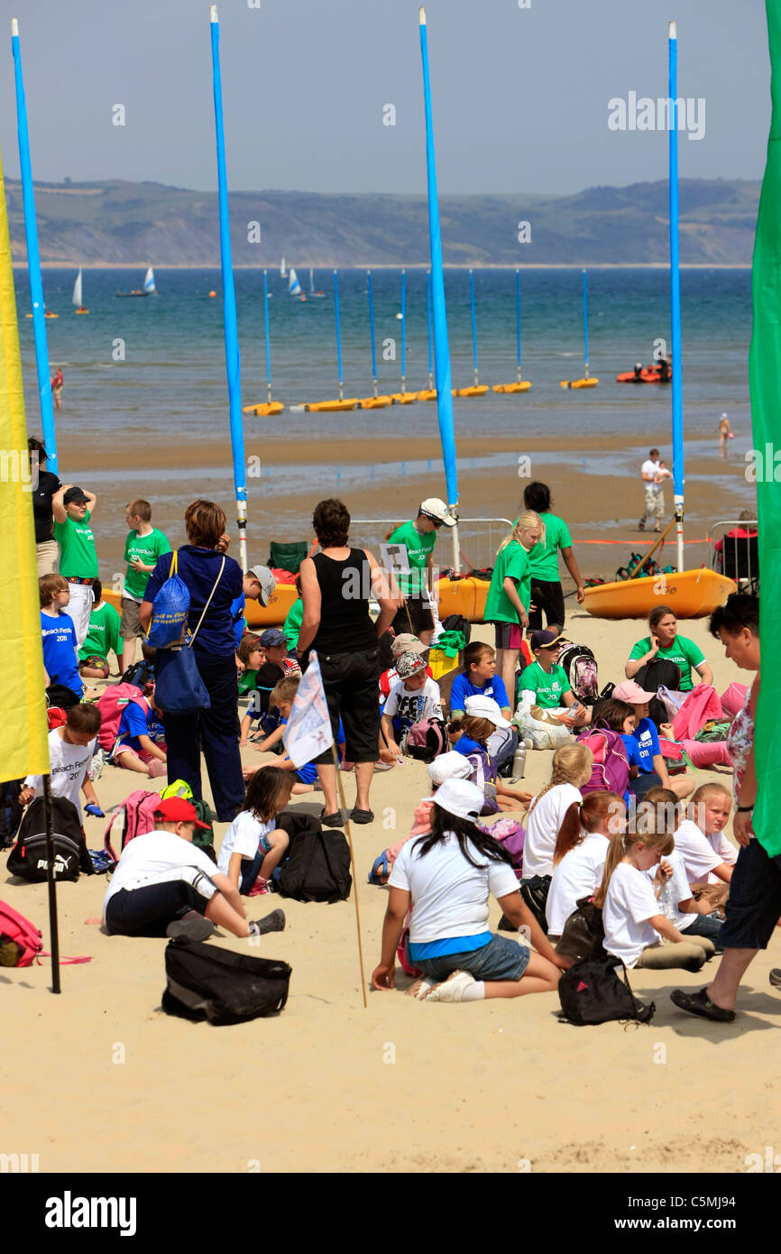 School children on the beach at Weymouth taking part in an outdoor education class Stock Photo