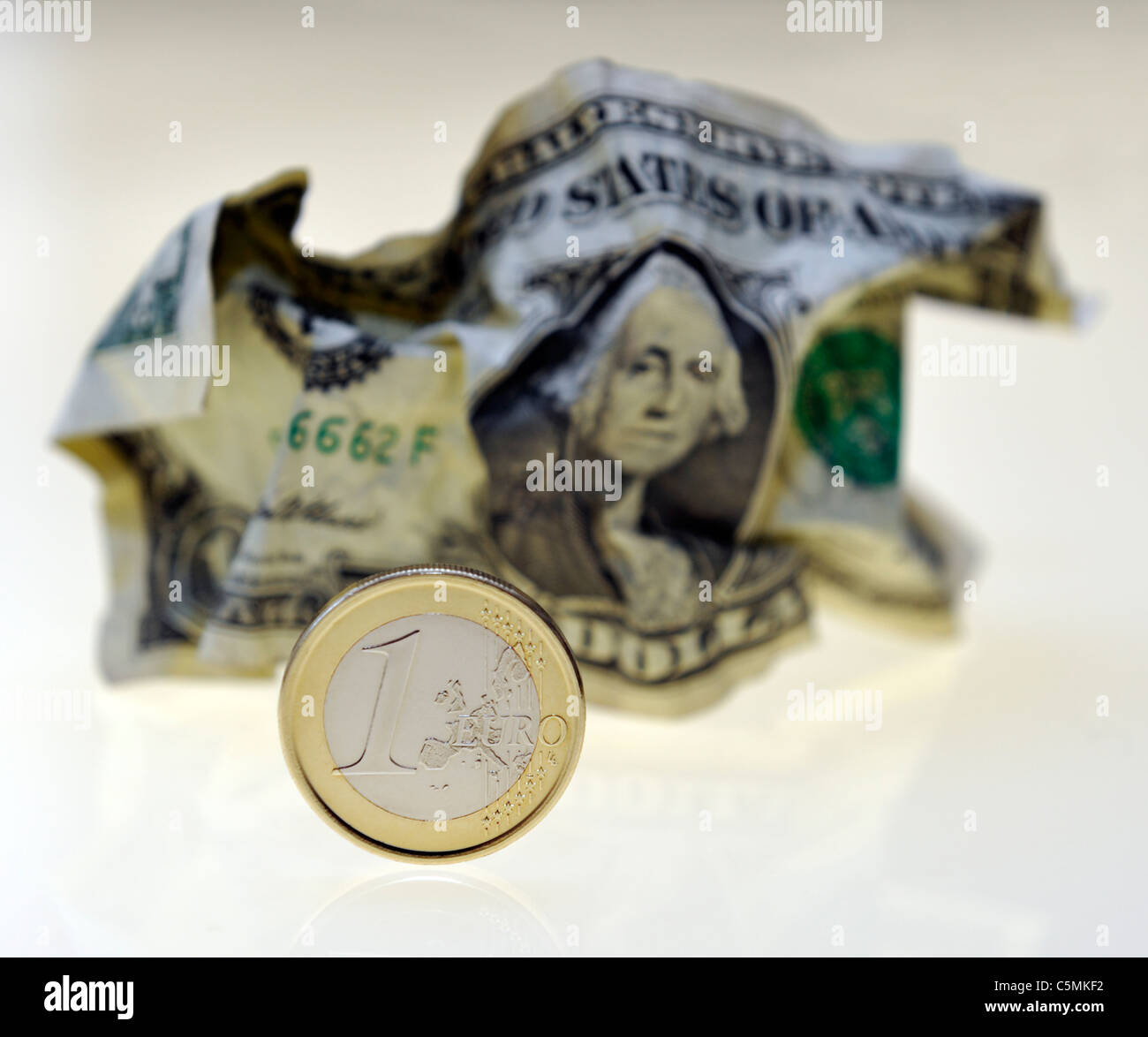 Euro Coin and crumpled Dollar Note - Stock Image