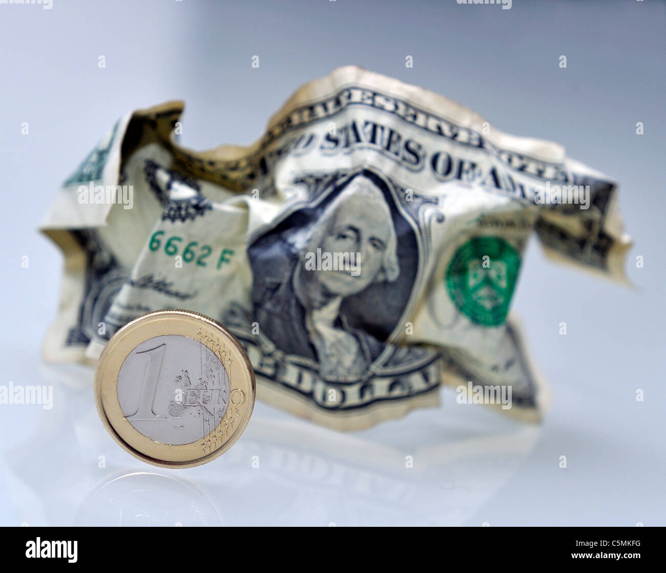 Euro Coin and crumpled Dollar Note Stock Photo