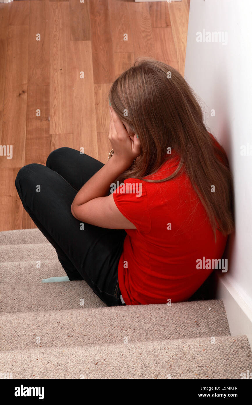 Young blonde female sitting alone on the stairs hands covering her face, back view. - Stock Image