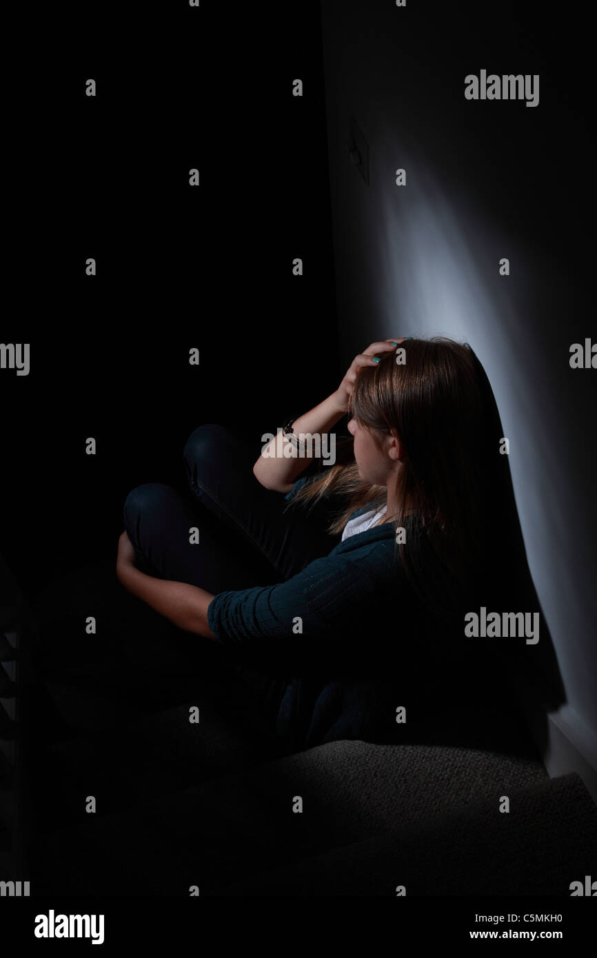 Young blonde female sitting alone in the dark, hand on head, back view. - Stock Image