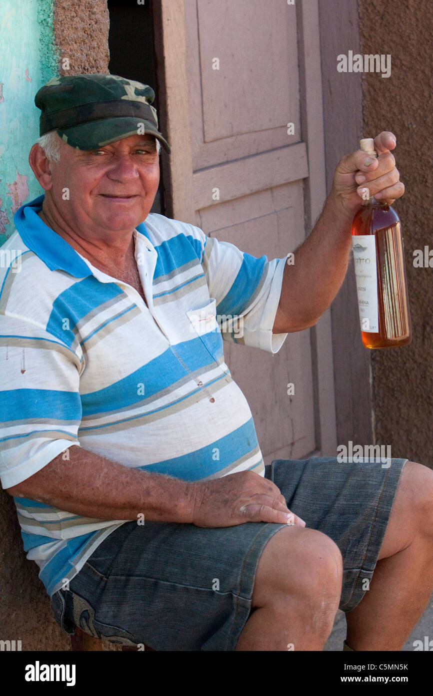 Cuba, Trinidad. Man Offering a Bottle of Honey for Sale. - Stock Image