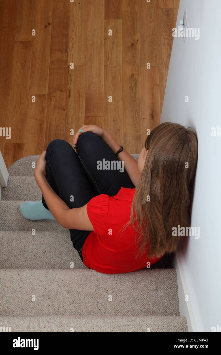 Depressed girl sitting on the stairs alone. - Stock Image