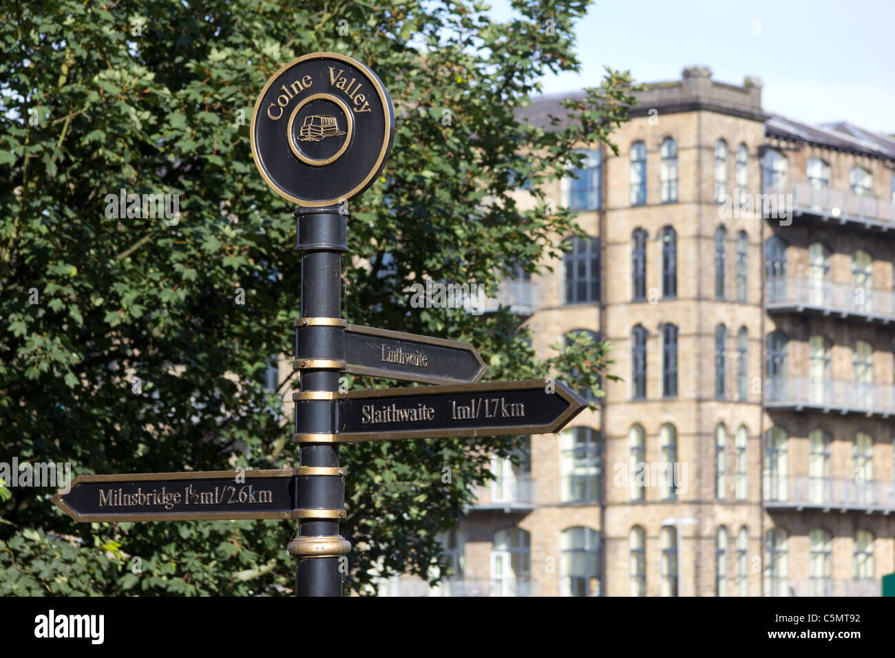 A signpost in the Colne Valley on the Huddersfield Narrow Canal; Titanic Mill Linthwaite defocussed in the background - Stock Image