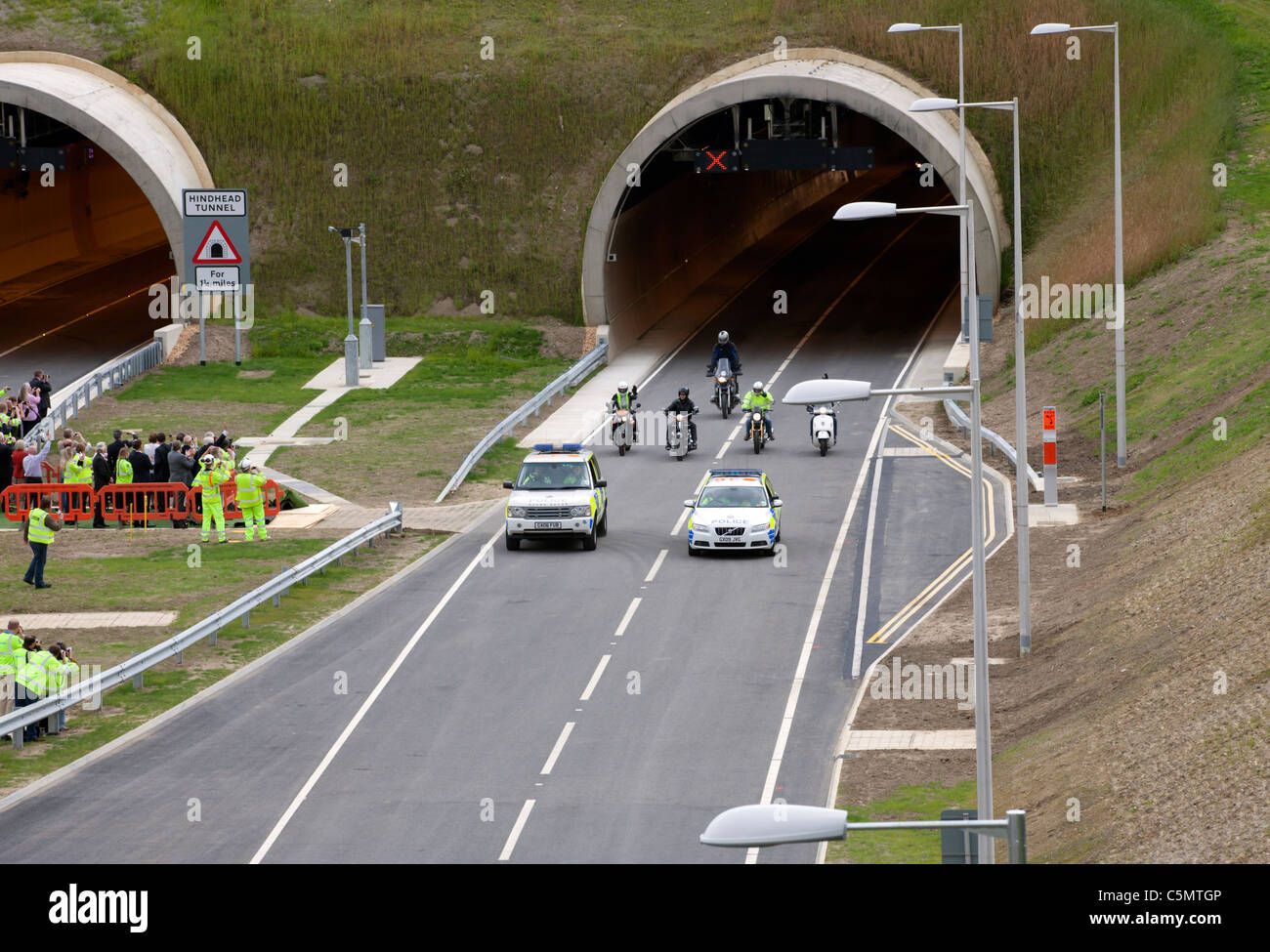 First traffic through the A3 Hindhead Tunnel. A rolling roadblock of 2 police cars and 5 motorbikes, watched by - Stock Image