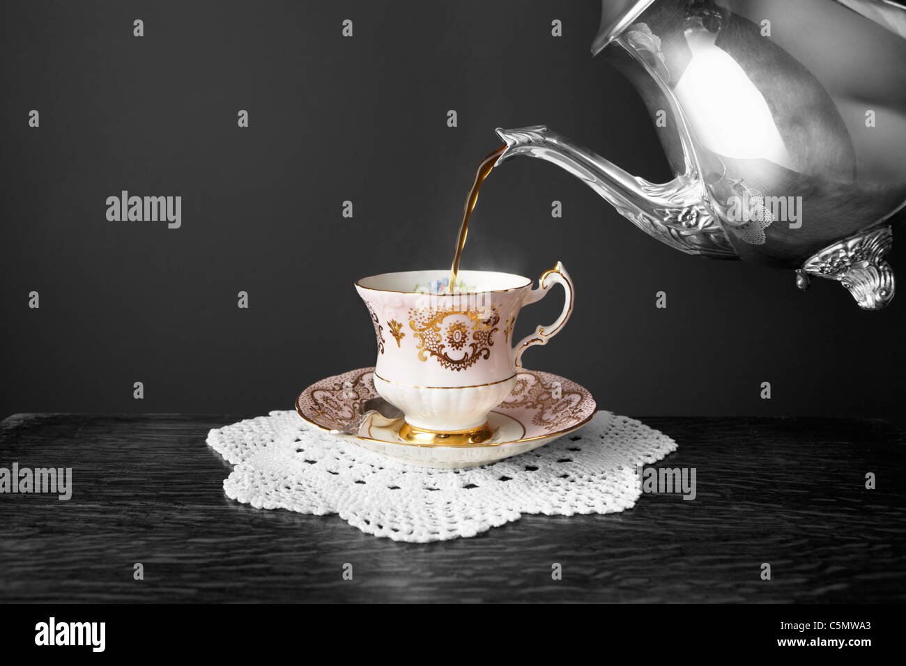 Pouring freshly brewed tea from a silver teapot into a vintage fine bone china tea cup.Stock Photo