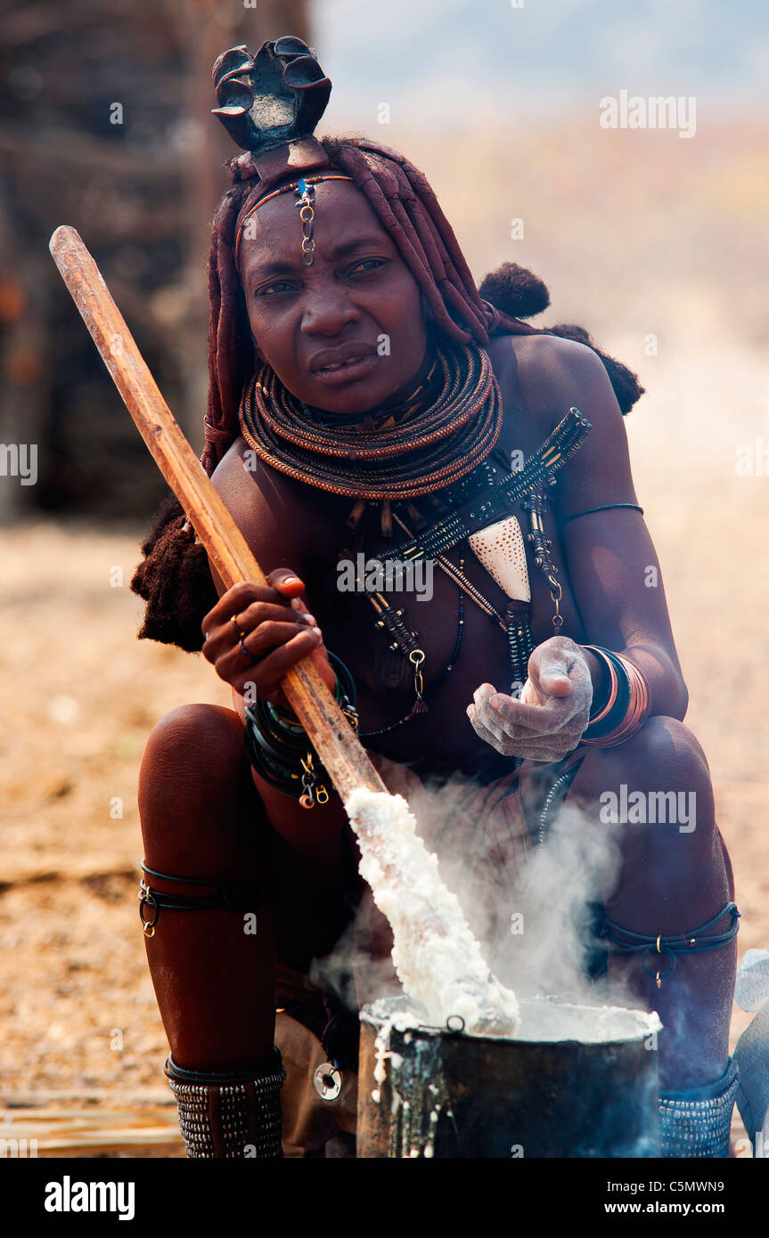 Himba woman cooking his traditional food made with wheat flour, Epupa Falls area, Kunene region, northern Namibia - Stock Image