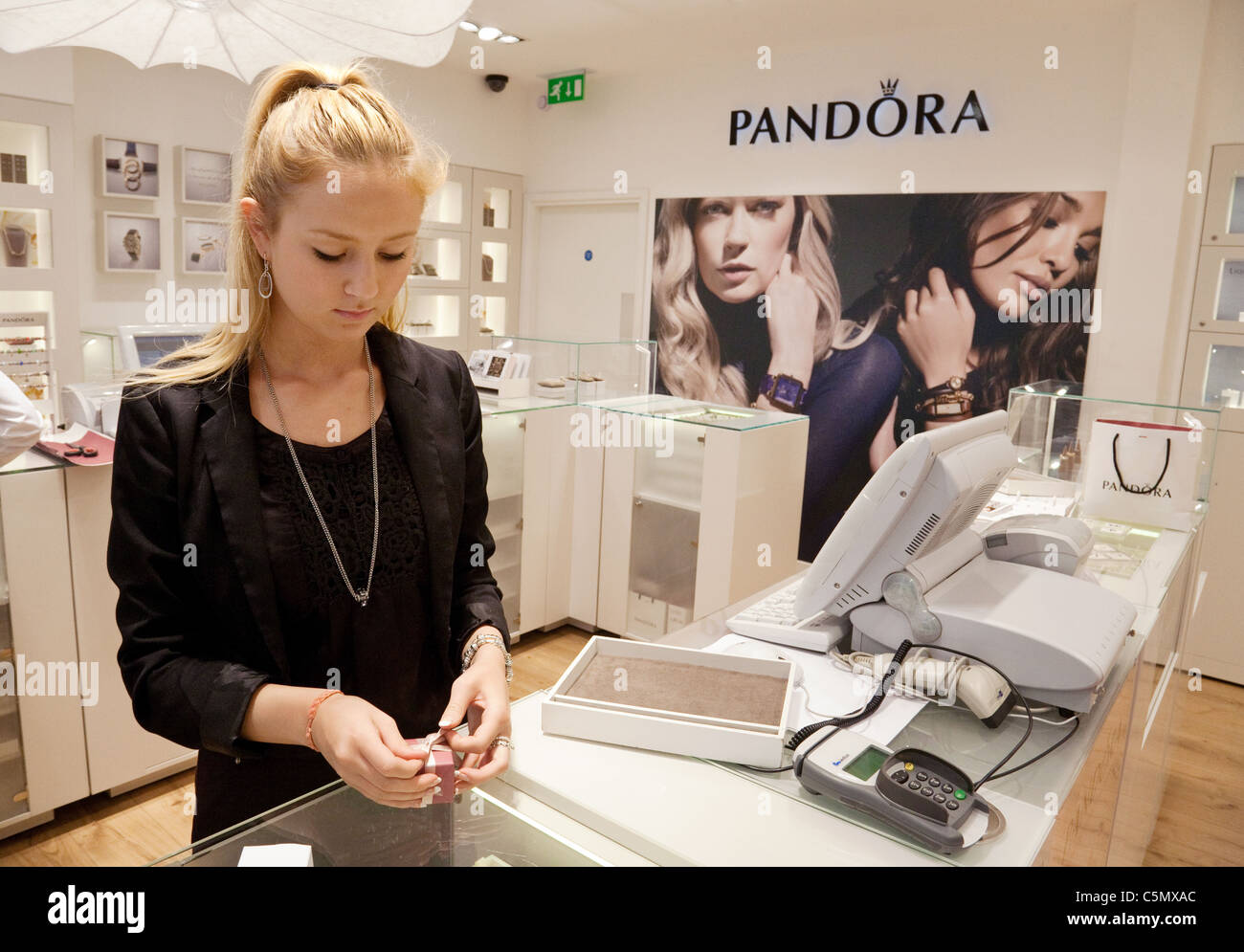A member of staff at Pandora jewellers wrapping a piece of jewellery, Pandora, Covent Garden, London UK - Stock Image