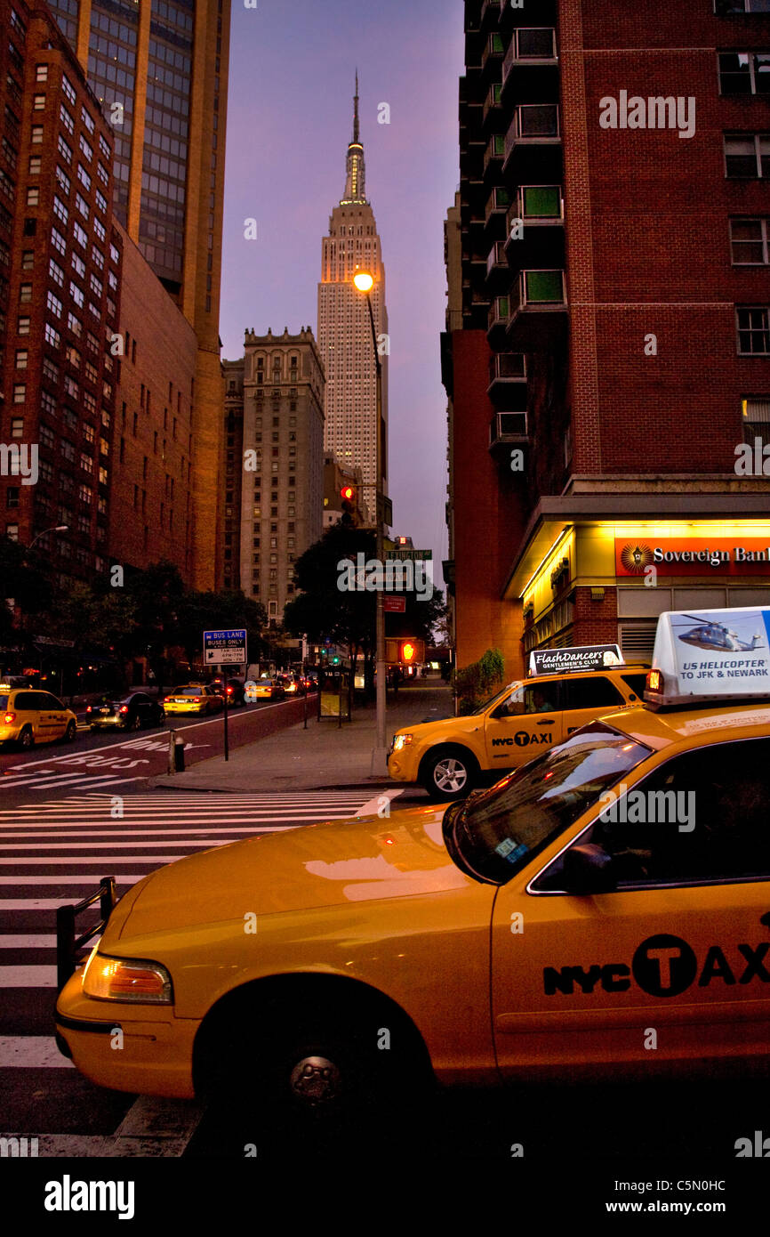 Street view with yellow taxi cabs towards empire state building at twilight, New York, USA - Stock Image