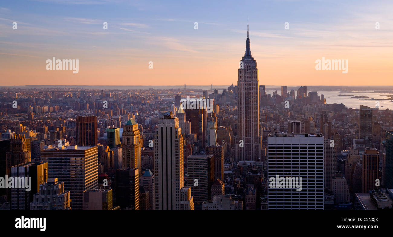View of city and Empire State Building from the Rockerfeller centre in the early evening light, New York, USA - Stock Image