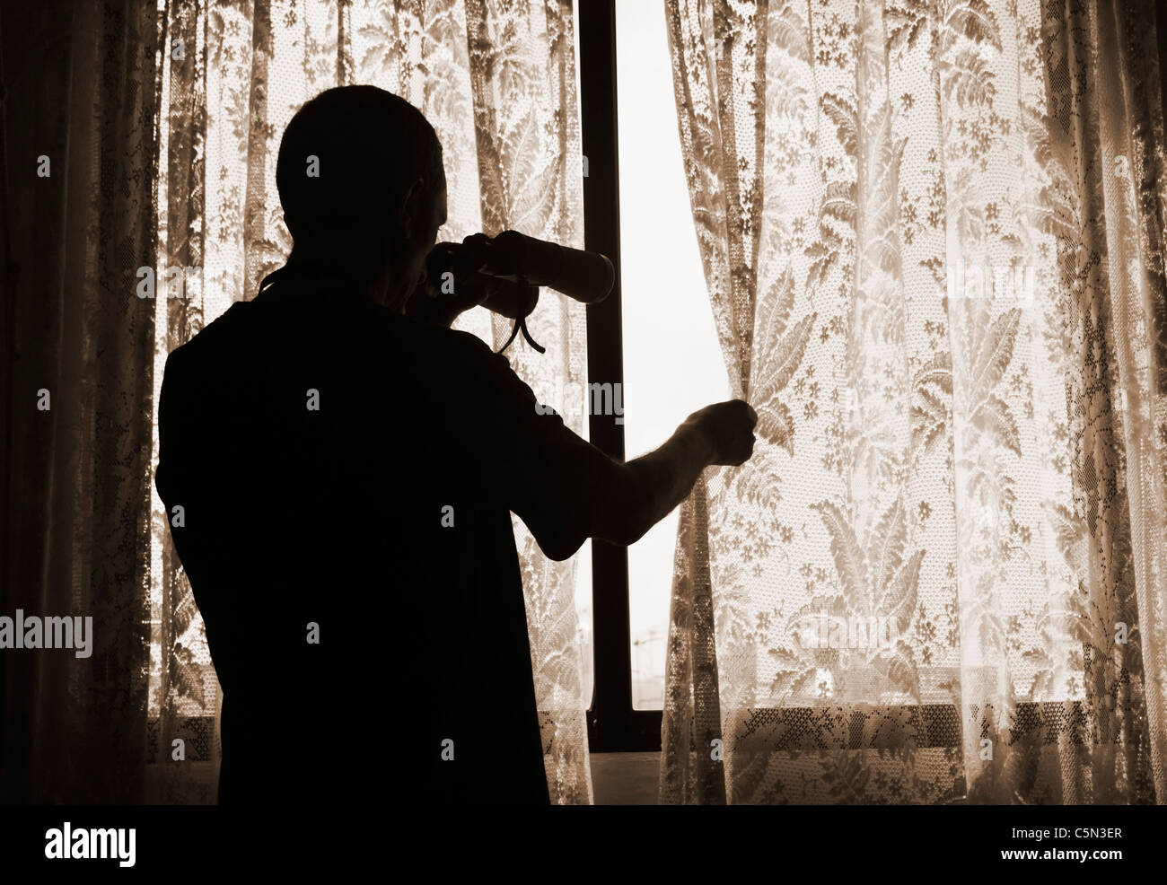 Man with binoculars looking out of window from behind net curtains - Stock Image