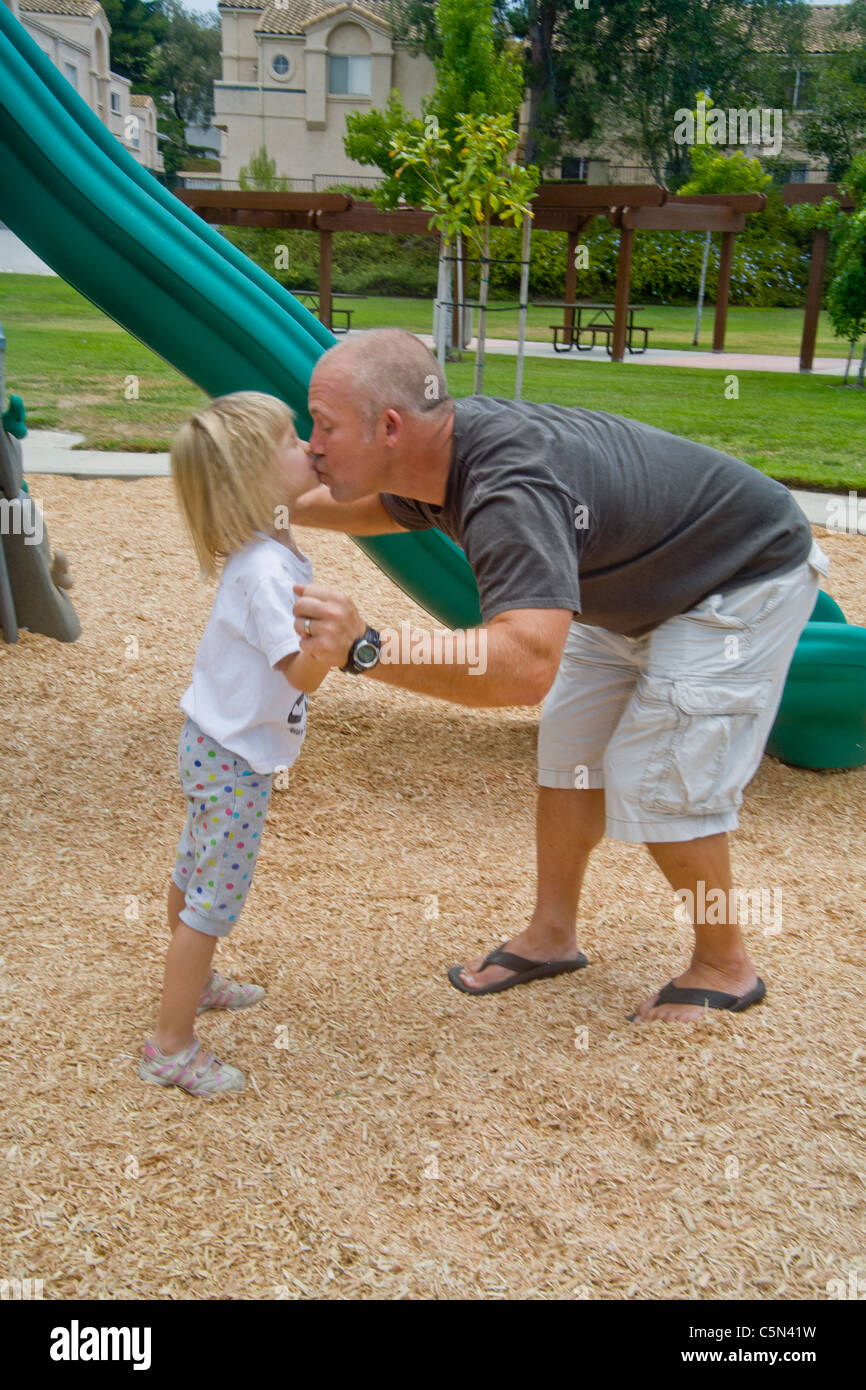 An affectionate father kisses his daughter while playing with her in a Lake Forest, CA, park. - Stock Image