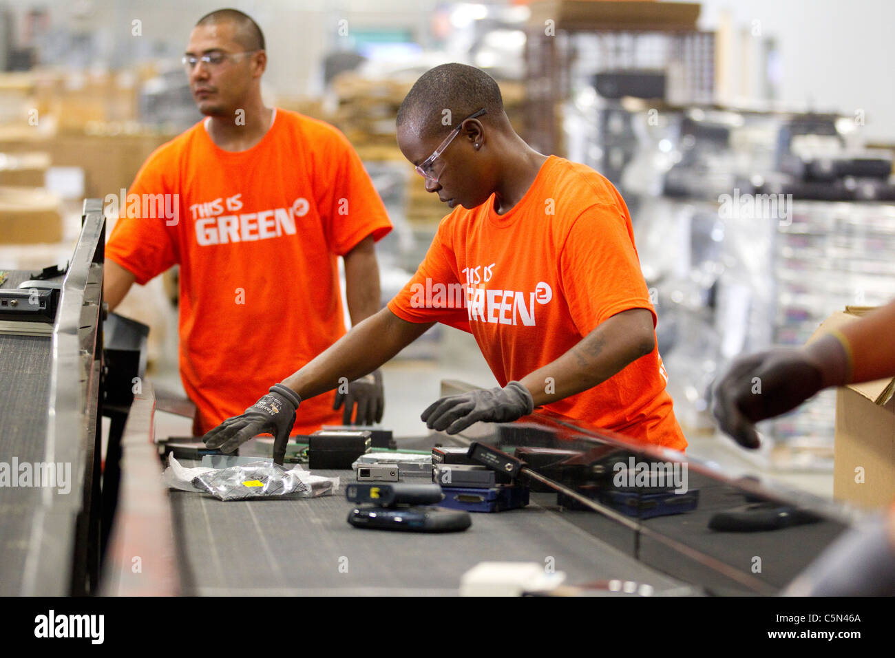 Blue-collar  workers at a recycler of outdated electronics and high tech devices, sort electronics in Austin for - Stock Image