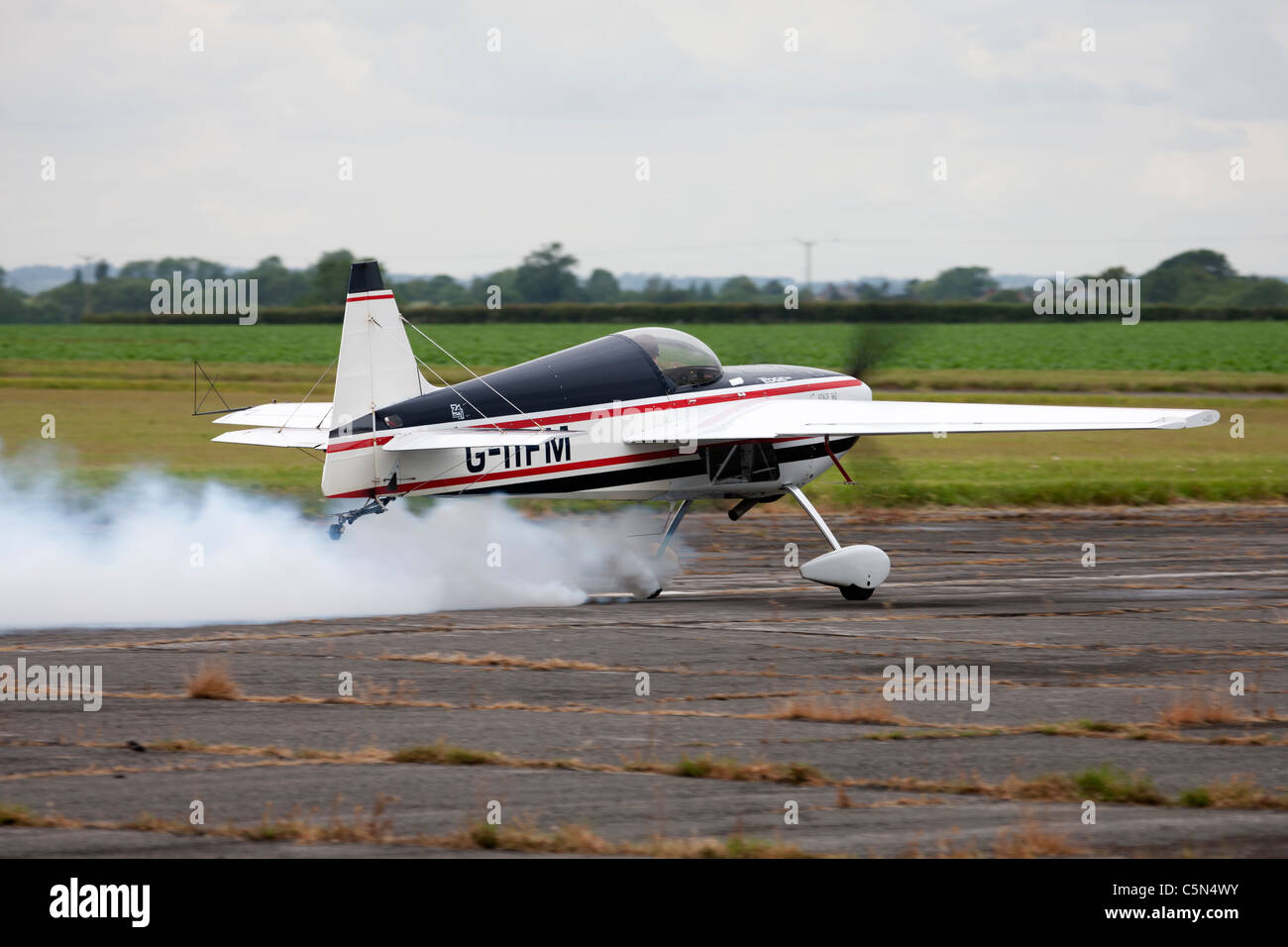 Edge 360 G-IIFM taking-off trailing smoke at Wickenby Airfield - Stock Image