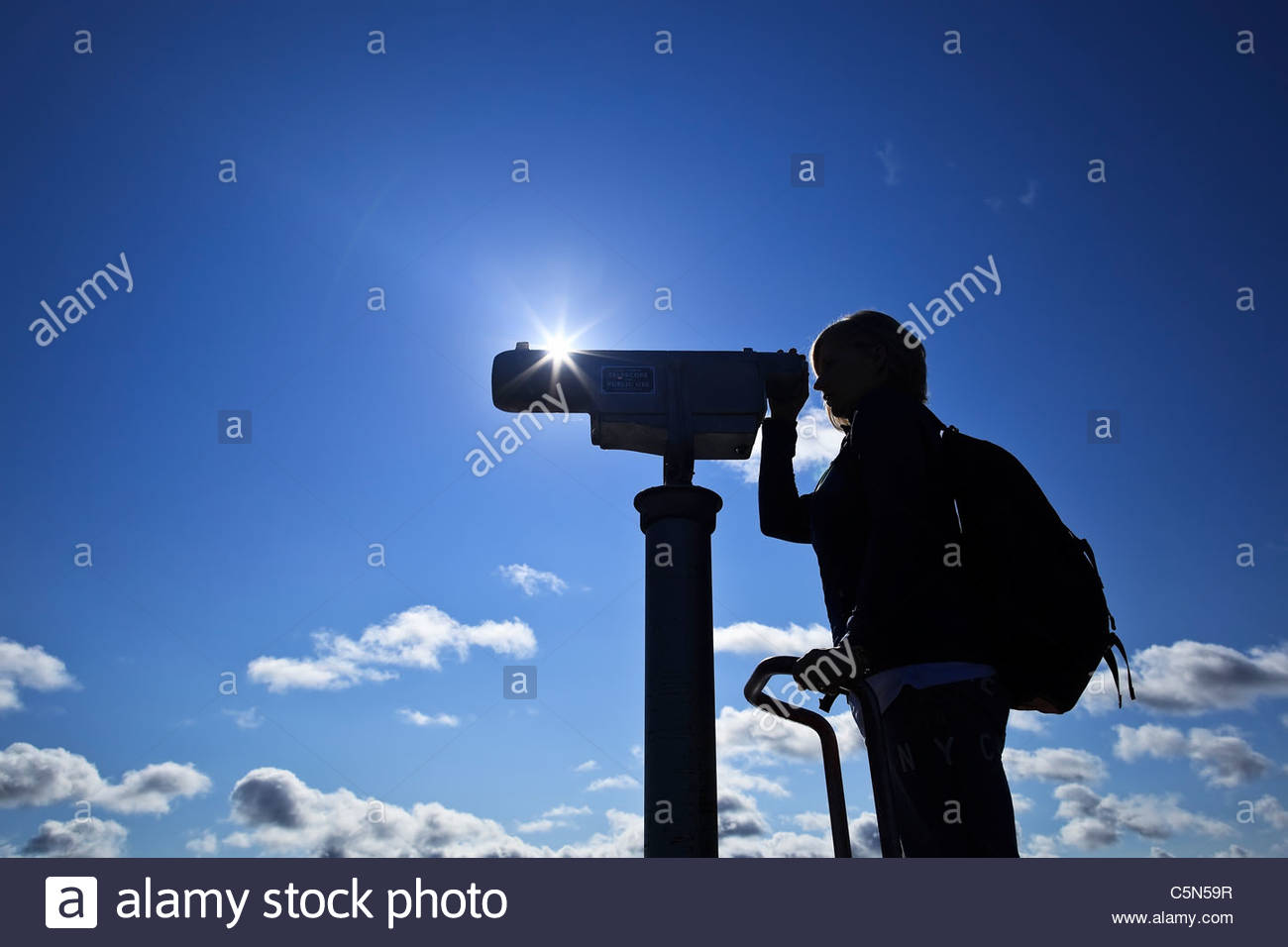 Woman looking through telescope, silhouette. - Stock Image