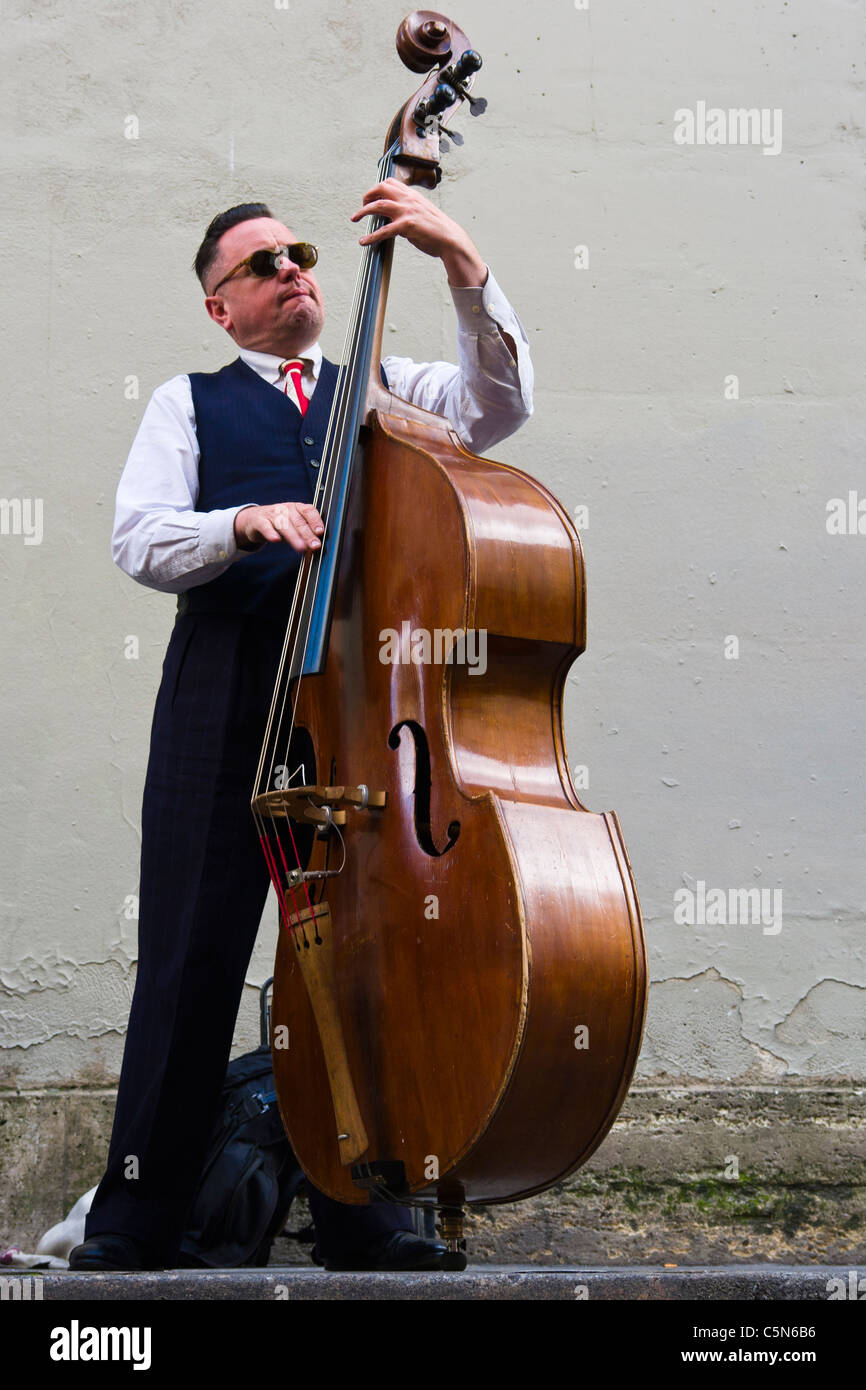 Double bassist busking as part of band in Paris, France - Stock Image