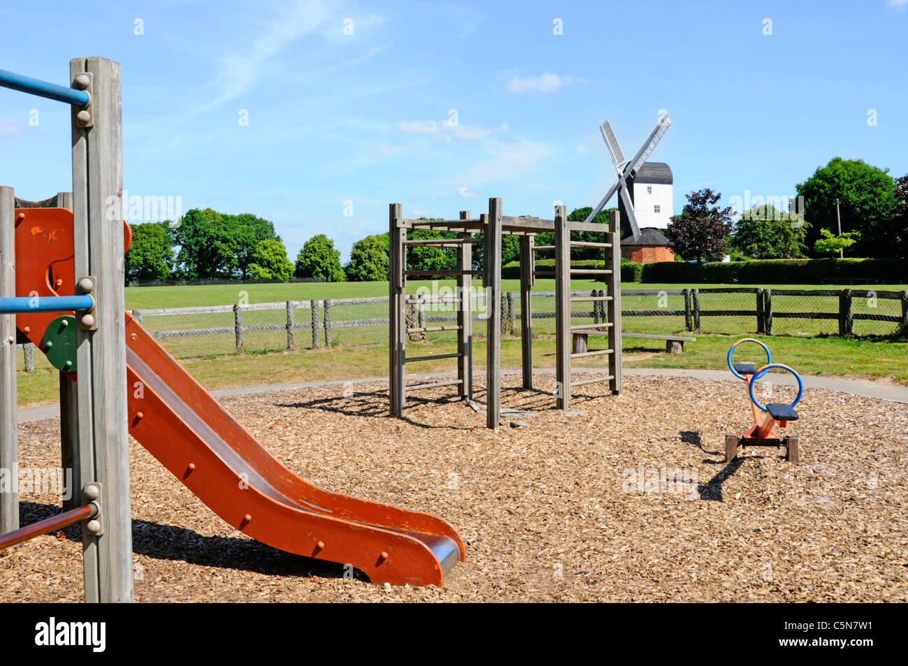 Playground slide  & climbing frame in fenced off children play area on village green with Mountnessing post mill Stock Photo