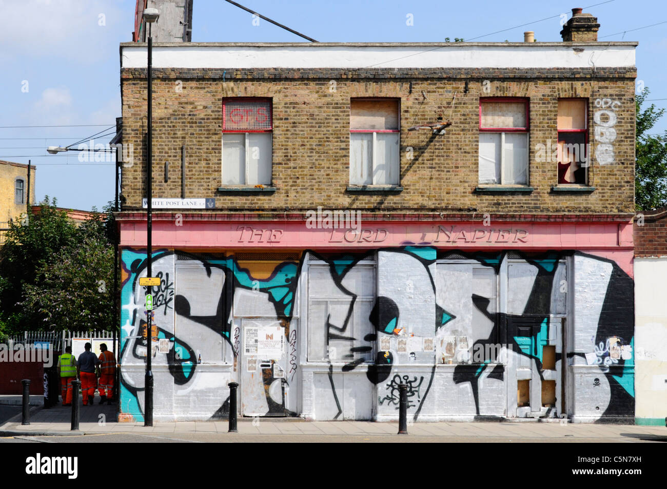East London street scene failed business redundant closed vandalised & boarded up pub building covered in street - Stock Image