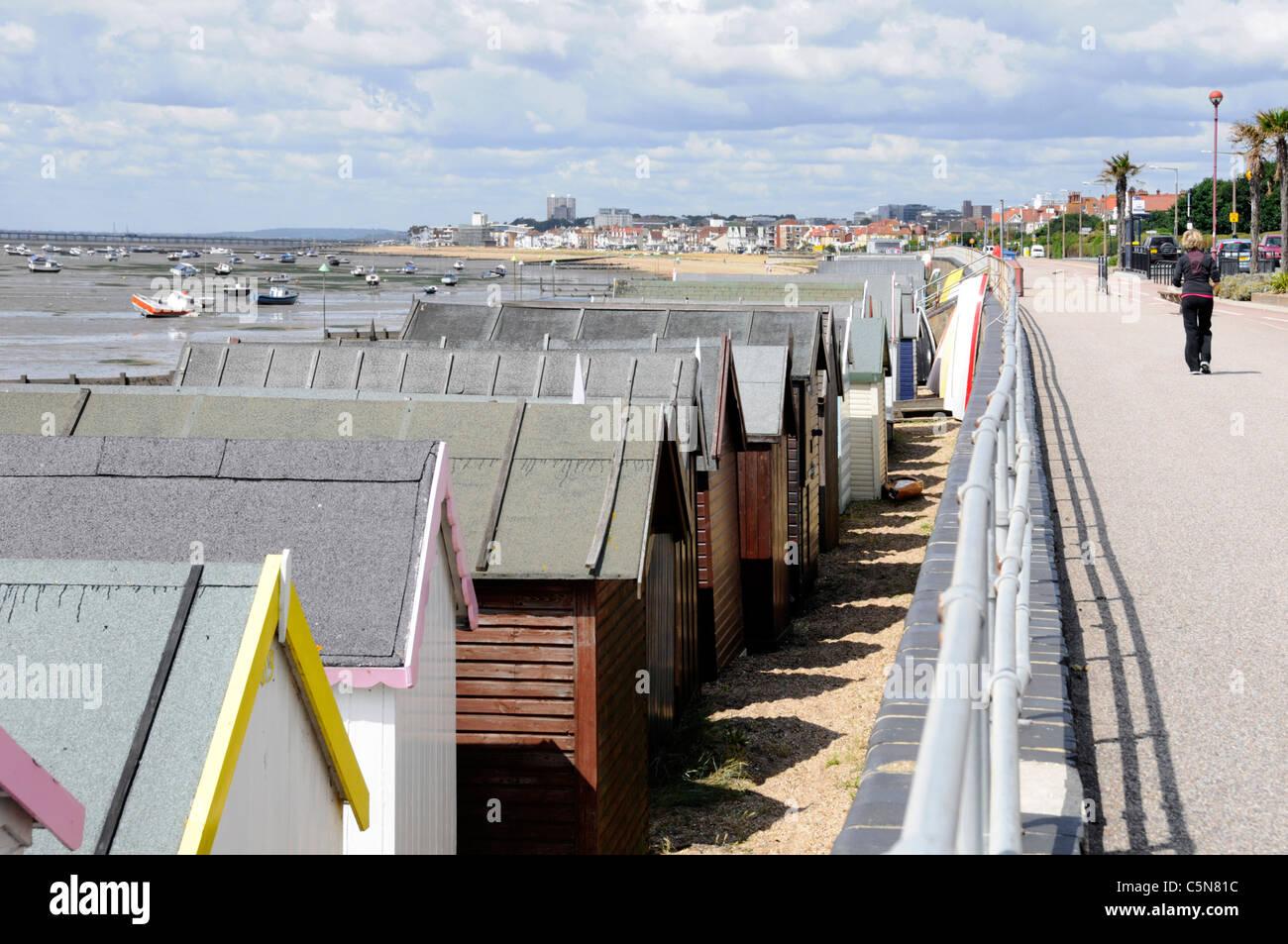 Seafront Beach Huts on sandy beach at Shoeburyness promenade & views towards Southend on Sea seaside resort - Stock Image