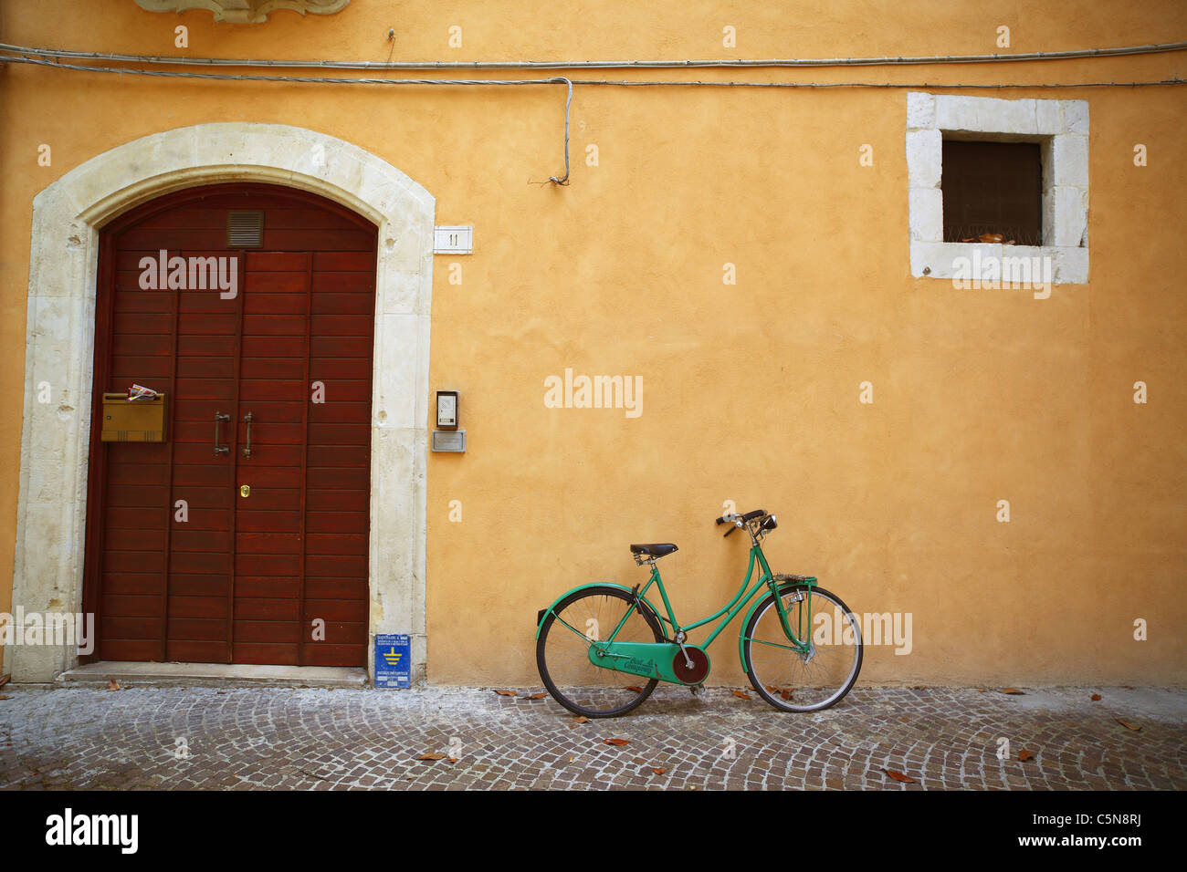 Green bicycle lent against a yellow ochre wall in Italy. - Stock Image