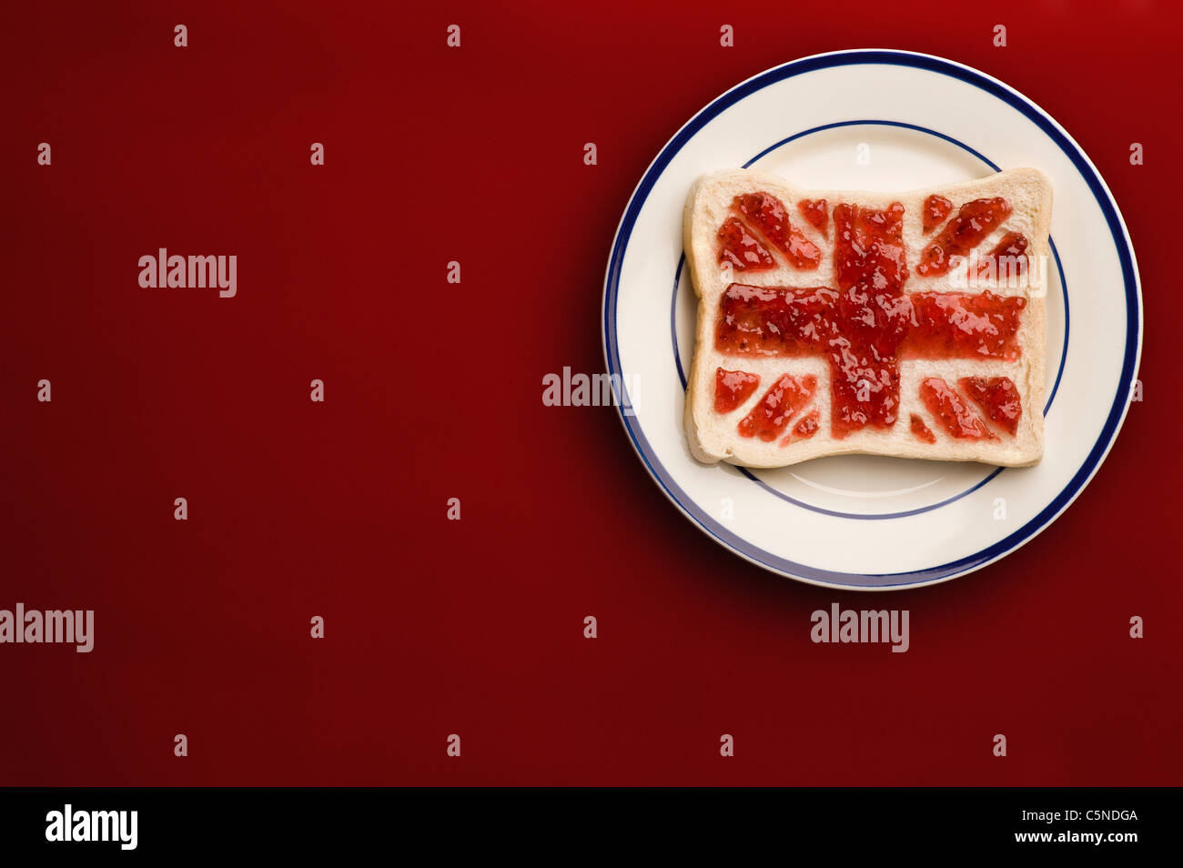 A slice of bread with a union jack flag of strawberry jam - Stock Image