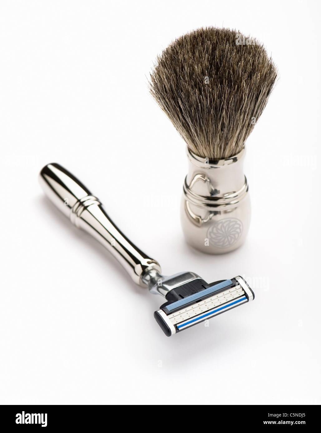 A silver razor and shaving brush - Stock Image