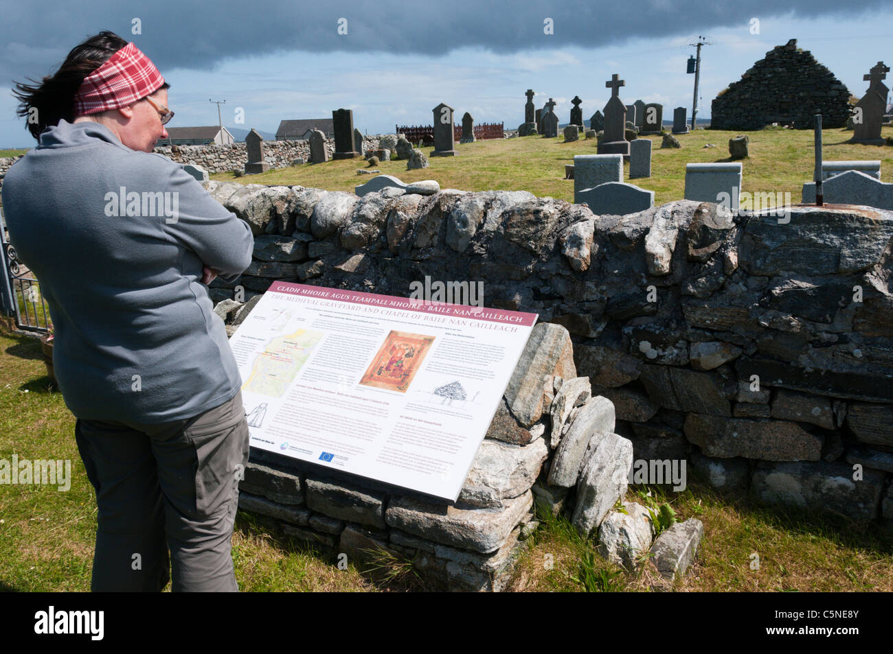A tourist reads an interpretative sign at Cladh Mhuire chapel and graveyard on Benbecula in the Outer Hebrides Stock Photo