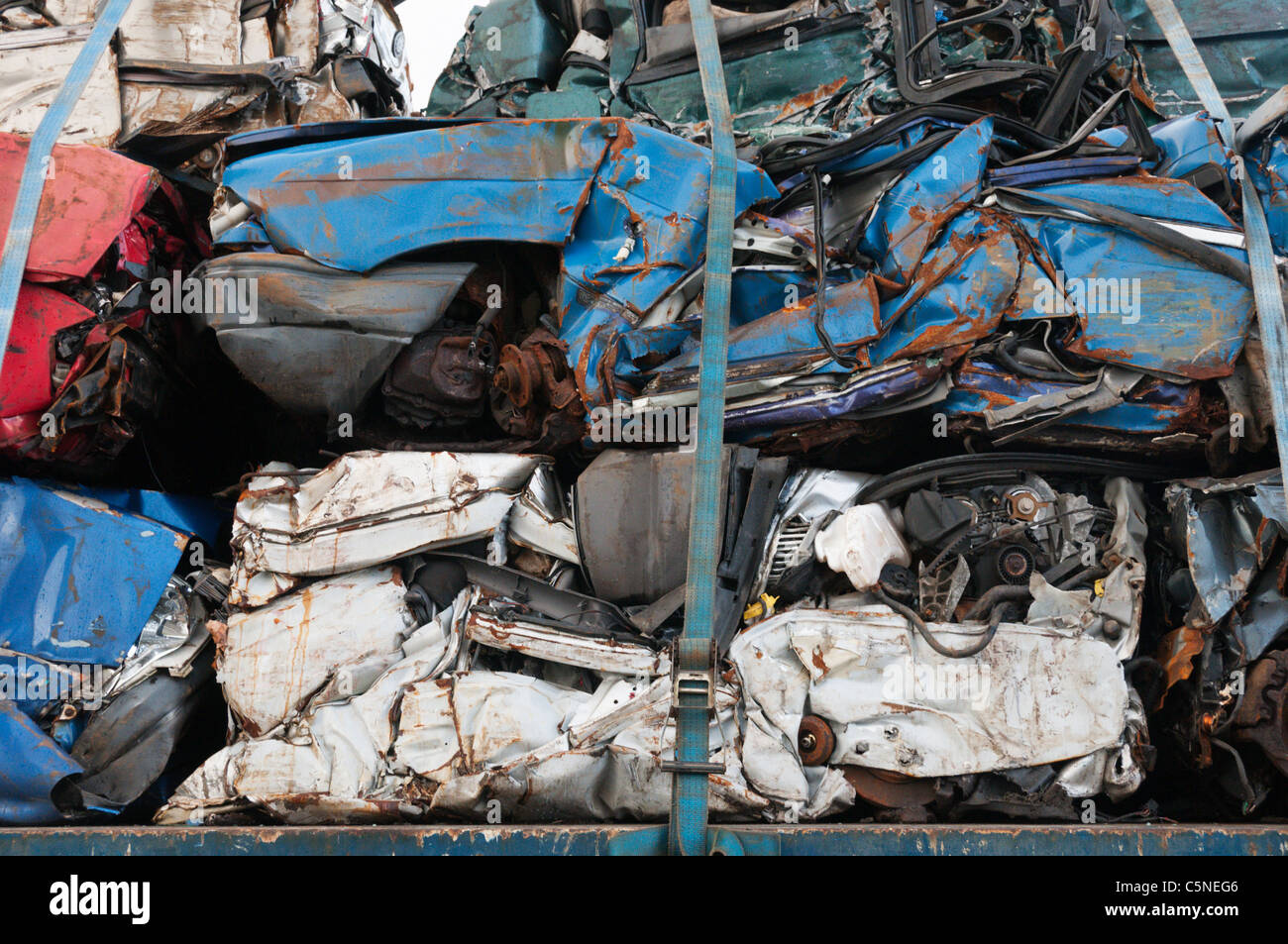 A pile of crushed car bodies strapped onto a transporter. - Stock Image