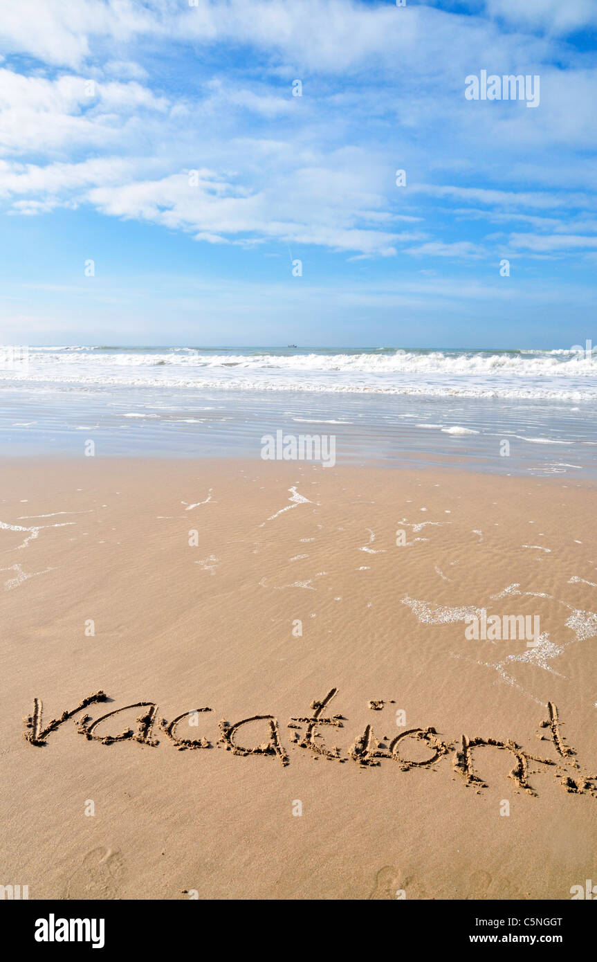 The word vacation, written in the sand of a beautiful beach - Stock Image