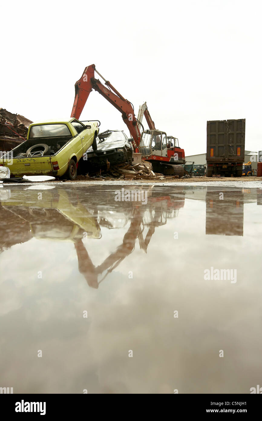 Scrapyard crane lifting scrap metal and cars for recycling reflected ...