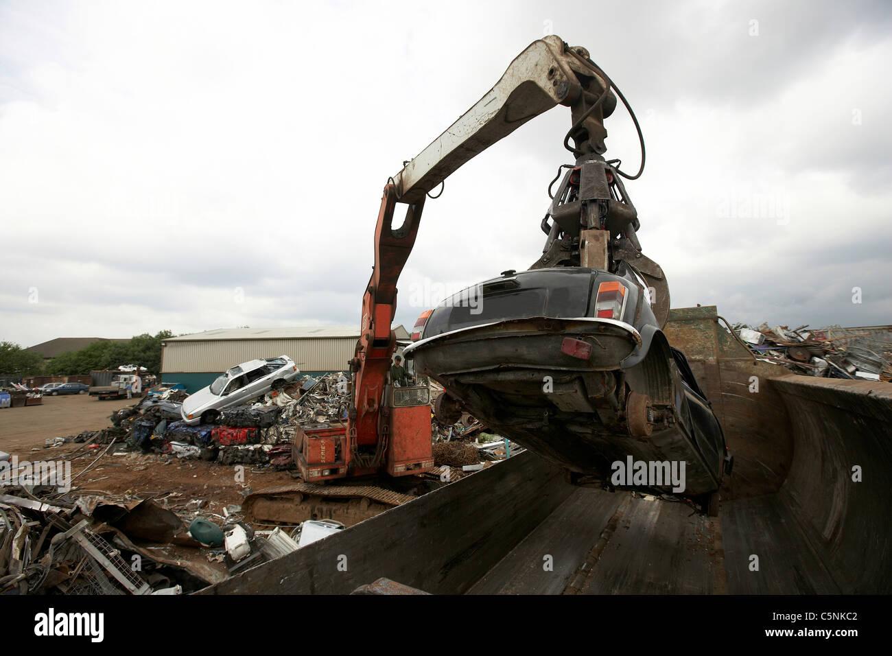 Crane lifting scrap car into a car crusher for recycling in a scrapyard, uk - Stock Image