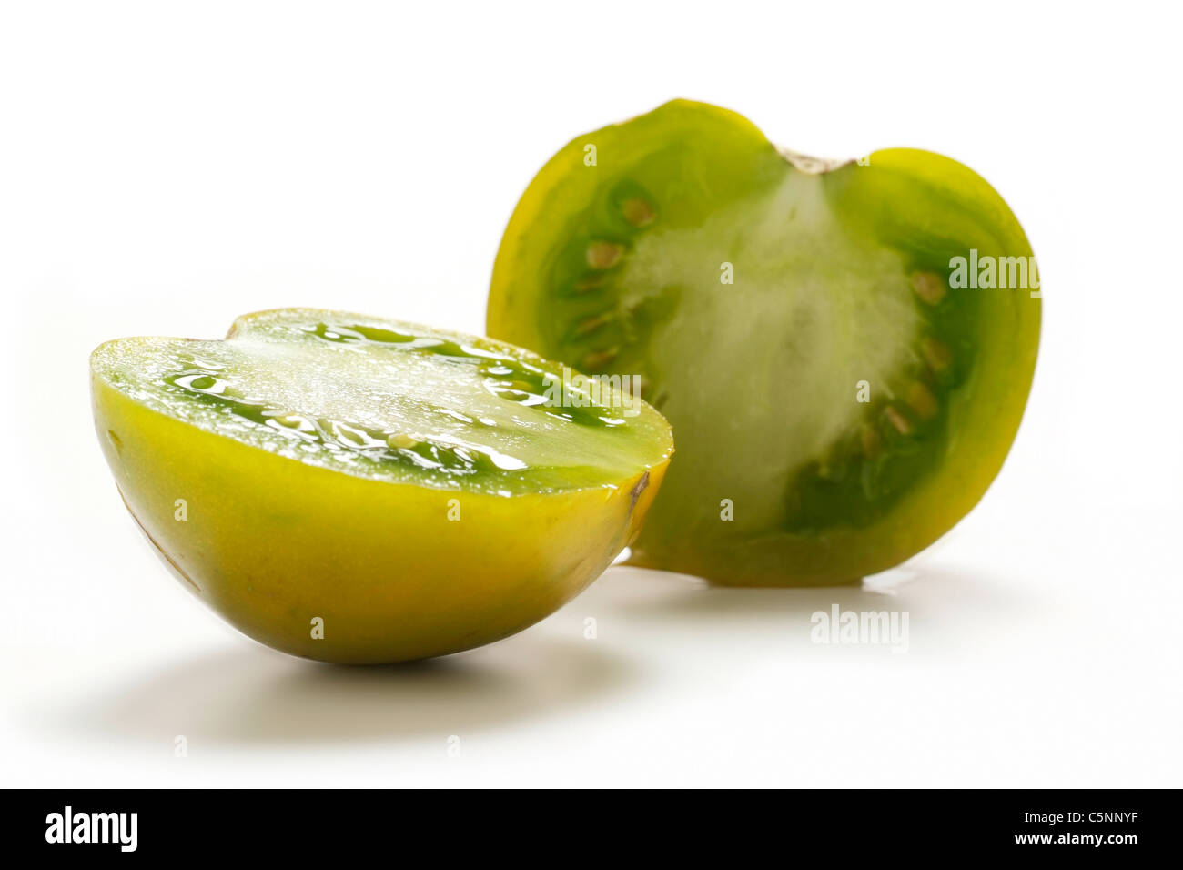Tomato varieties:  Lime Green, two halves - Stock Image