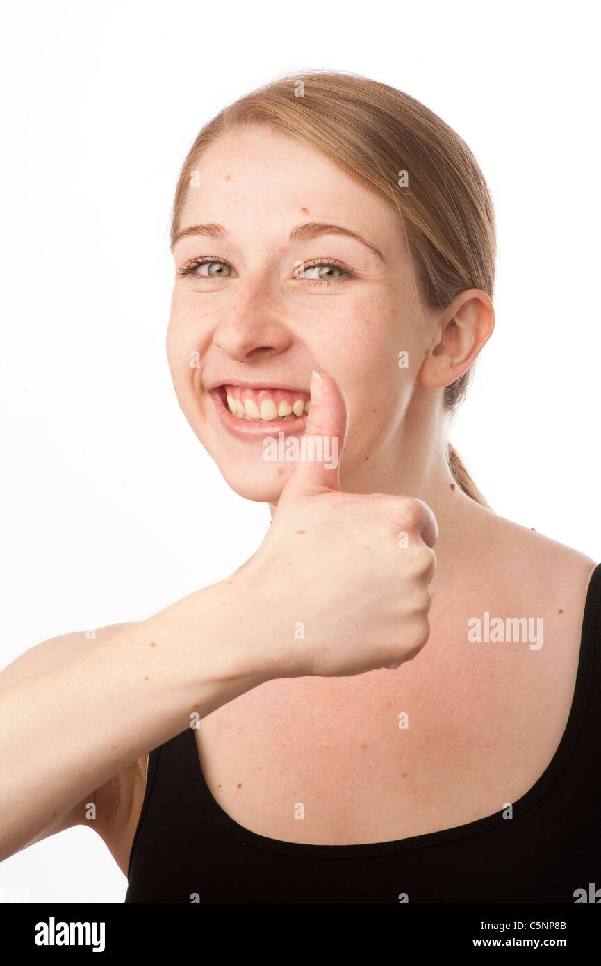 a young caucasian woman with her thumbs up looking positive, uk - Stock Image